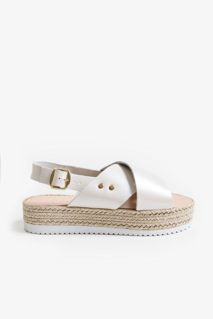 An off-white leather sandal with crossover straps, a plimsole platform sole, and a pearl finish