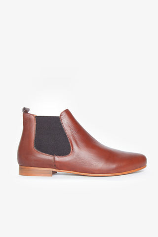 An everyday flat slip-on leather boot with elasticised panels and a slightly pointed toe. Low wooden block heel.