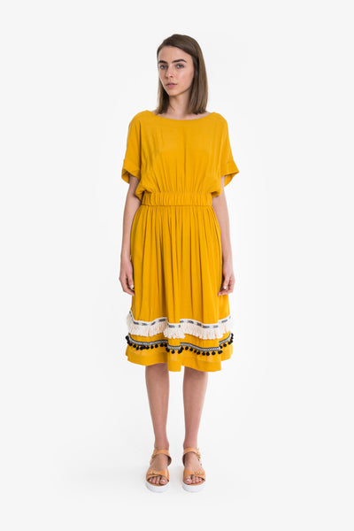 A scoop neck dress with kimono sleeves, gathered elastic waist and pom-pom trim. Available in mustard sunflower yellow and rich inky blue.