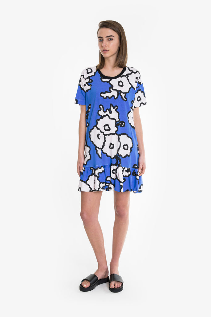 A bold and bright blue and white floral print jersey cotton tshirt dress from Obus. Boxy fit, scoop neck, finishes above the knee with a ruffle.