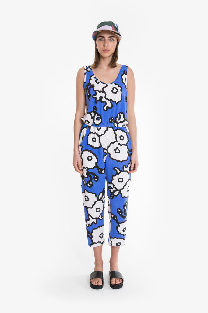 A bold and bright blue and white floral sleeveless jersey cotton jumpsuit from Obus. Elastic waist, scoop neck, pockets. Above ankle length.
