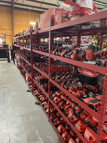 A row of shelves full of used power tools for sale.