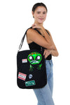 Peeking Alien Canvas Messenger Bag, shoulder bag style on model