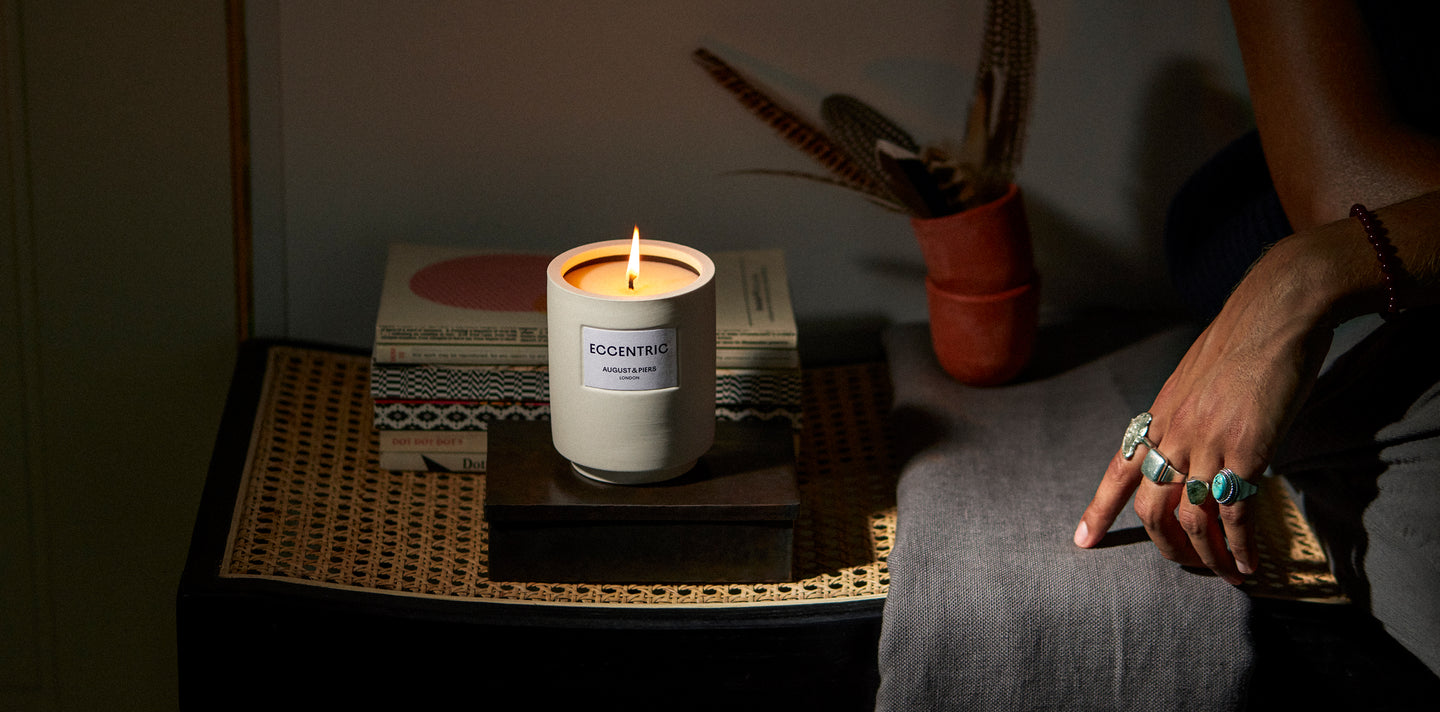 Eccentric luxury fragranced candle, styled on a rattan bench next a stylish hand decorated in silver rings.