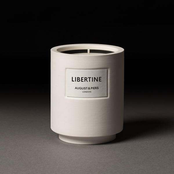 AUGUST&PIERS 340g Libertine scented candle with fragrance notes of cedarwood, patchouli and guaiac wood in white ceramic vessel.