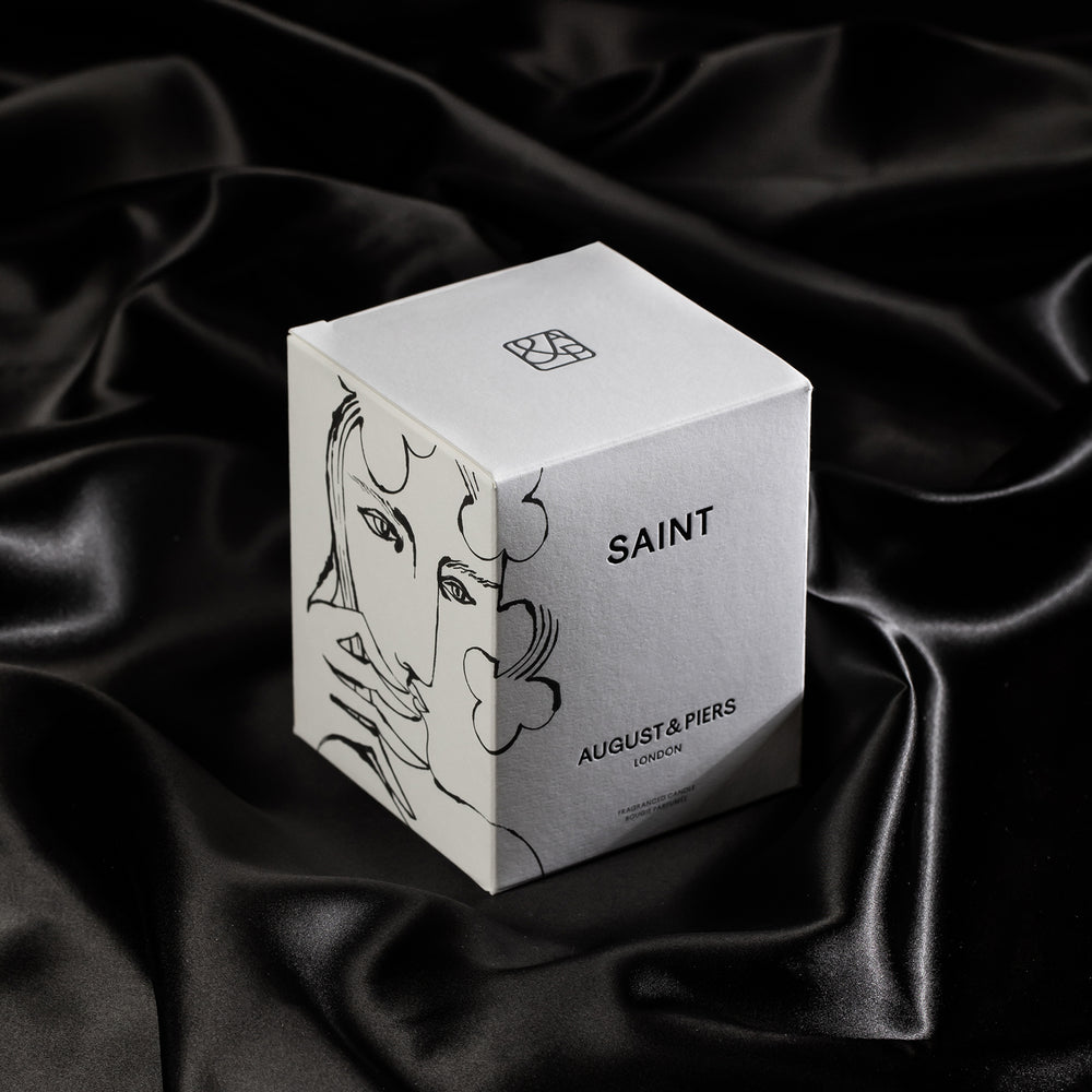 Saint luxury scented candle on black satain, displaying white packaging showing petra börner illustration.