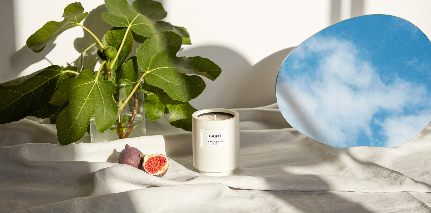 Saint luxury fragranced candle situated on linen cloth table next to wild fig leafs and an oval mirror reflecting the sky.