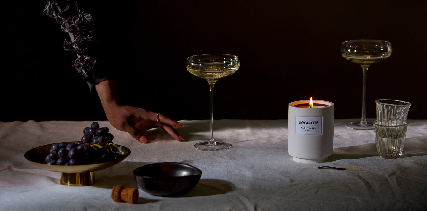 Socialite luxury fragranced candle situated on a grey cloth table surrounded by champagne flutes and black grapes in a brass dish.