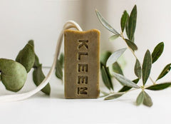 A green coloured bar of Kleen's soap on a rope with foliage either side