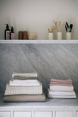 Aerende's textile and ceramics collection in a marble tiled bathroom