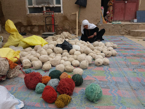 a woman sorting through balls of wool on the floor outside