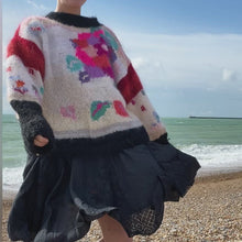 Load and play video in Gallery viewer, 1980s floral jumper, navy skirt and tan boots on redhead model at the beach, sea in background