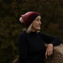 Load image into Gallery viewer, Older blonde model in Thread Tales recycled cashmere bobble hat in red against autumnal background