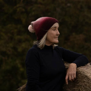 Older blonde model in Thread Tales recycled cashmere bobble hat in red against autumnal background