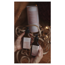 Load image into Gallery viewer, Two hands holding LA-EVA's ROSĒUM wash and lotion pair with cylindrical packaging and twinkly lights in background