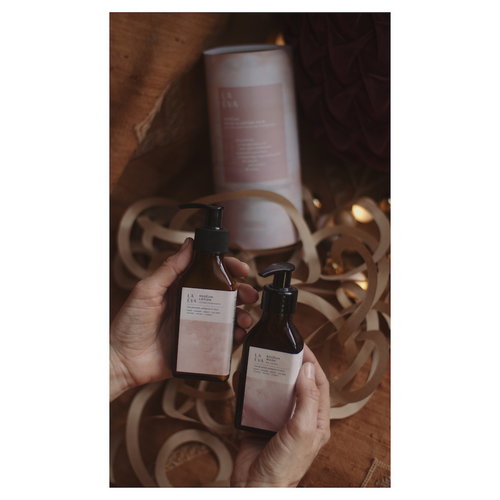 Two hands holding LA-EVA's ROSĒUM wash and lotion pair with cylindrical packaging and twinkly lights in background