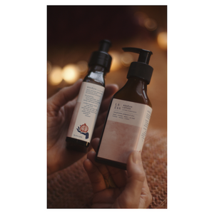 Two hands holding LA-EVA's ROSĒUM wash and lotion pair with blanket and twinkly lights in background