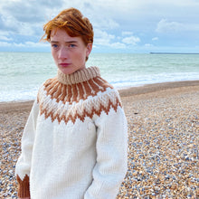 Load image into Gallery viewer, Close-up of redhead girl standing on the beach with the sea in background wearing a cream, beige and rust-coloured jumper
