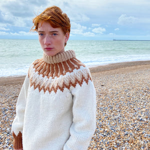 Close-up of redhead girl standing on the beach with the sea in background wearing a cream, beige and rust-coloured jumper