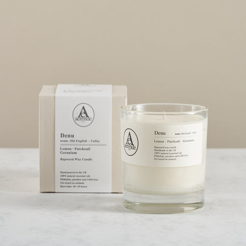 Aerende Denu candle boxed and packaged alongside unwrapped version in glass
