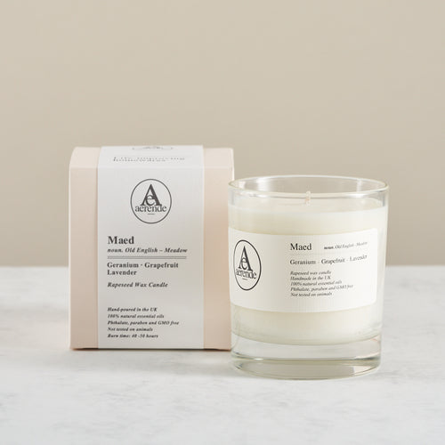 Aerende Maed candle boxed and packaged alongside unwrapped version in glass