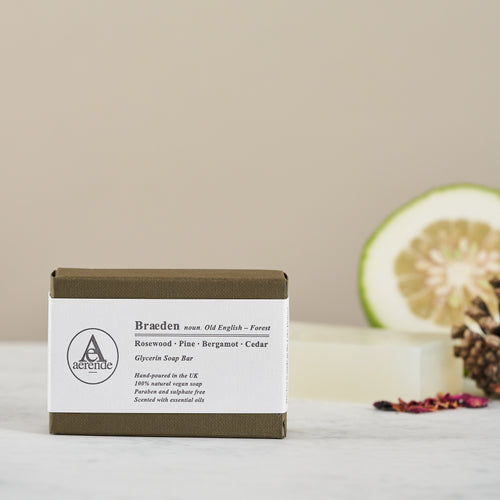Bar of Braeden soap in khaki and white paper packaging with grapefruit half in background