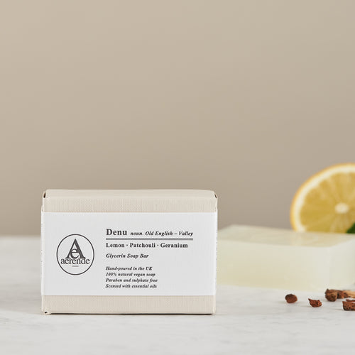 Aerende's Denu soap in white and cream paper packaging with an unwrapped soap and lemon half in background