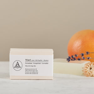 Bar of Aerende's Maed soap in cream and white paper packaging with an unwrapped soap, orange and lavender in background