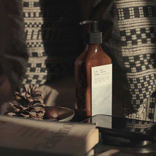 Load image into Gallery viewer, LA-EVA BLÜ lotion in brown apothecary bottle surrounded by rattan textiles, books and a brass bowl with pine cones and chestnuts