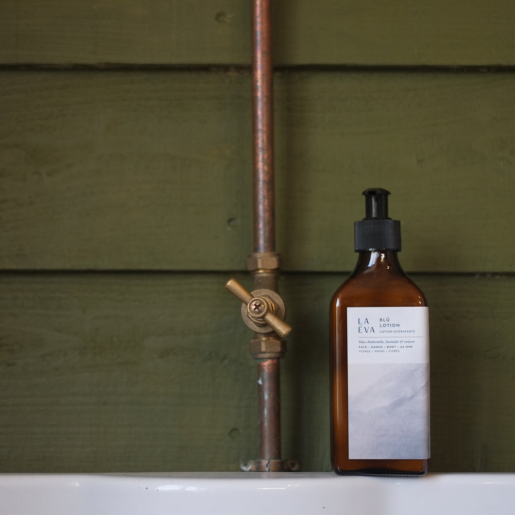 LA-EVA BLÜ lotion in brown apothecary bottle against forest green shiplap panels and copper pipe on white shelf