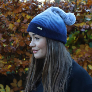 Brunette model in Thread Tales recycled cashmere bobble hat in blue, against autumn background