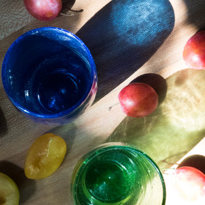 Aerial view of Ishkar's handblown coloured glass tumblers on wooden surface with fruit