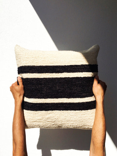 Two arms holding black and cream centre stripe cushion