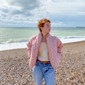 Redhead model on the beach with the sea in the background wearing Bobby Spot puffer jacket, the Earhart camisole, blue jeans and tan belt