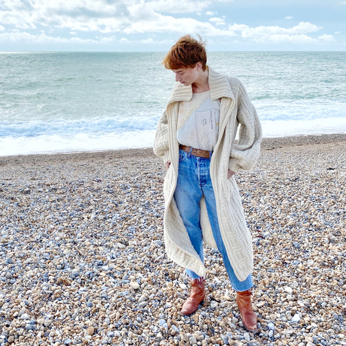 Redhead model on beach with sea in background wearing Earhart cami, blue jeans, tan belt and boots and an oversize cream knitted cardigan