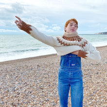 Load image into Gallery viewer, Redhead girl standing on the beach with the sea in background removing a cream, beige and rust-coloured jumper. Blue denim dungarees beneath