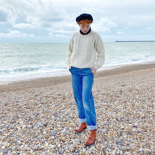 Redhead model on beach with sea in background wearing beret, aran jumper, blue rolled up jeans and tan boots
