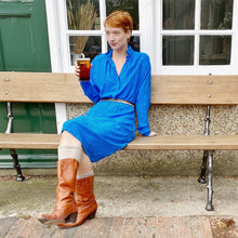 Load image into Gallery viewer, Redhead model on bench outside pub holding pint, wearing sapphire blue vintage silk dress and tan cowboy boots