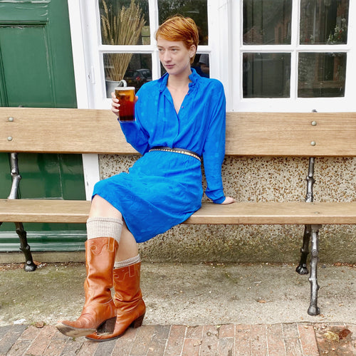Redhead model on bench outside pub holding pint, wearing sapphire blue vintage silk dress and tan cowboy boots