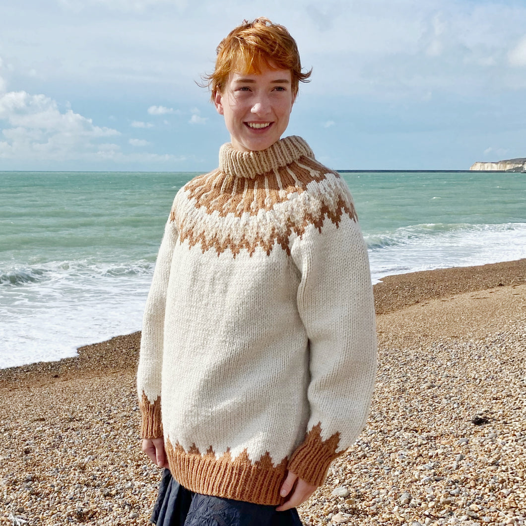 Redhead girl standing on the beach with the sea in background wearing a cream, beige and rust-coloured jumper