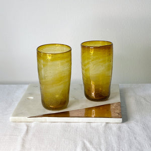 Two Ishkar tall gold tumblers on a white and gold tile on a white cloth with white background