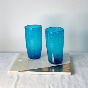 Two Ishkar tall turquoise tumblers on a white and gold tile on a white cloth with white background