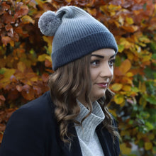 Load image into Gallery viewer, Brunette model in Thread Tales recycled cashmere bobble hat in grey, against autumn background