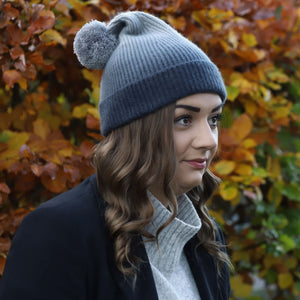 Brunette model in Thread Tales recycled cashmere bobble hat in grey, against autumn background