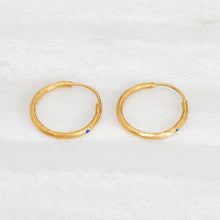 Load image into Gallery viewer, Ishkar's gold-plated hoop earrings with lapis lazuli detail on white background