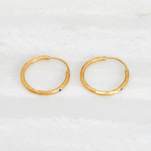 Ishkar's gold-plated hoop earrings with lapis lazuli detail on white background