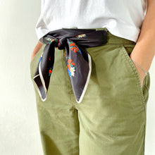 Load image into Gallery viewer, Close up of floral vintage scarf tied as a belt on model with white top and green trousers