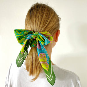 Bright green psychedelic scarf tied in a bow on blonde model's hair