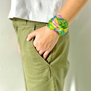 Hand in khaki trouser pocket with bright green psychedelic scarf tied around wrist