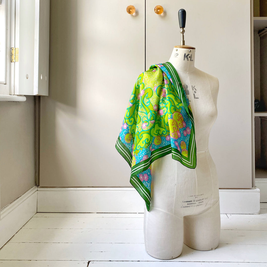 Bright green scarf over shoulder of tailor's dummy sitting on painted floor